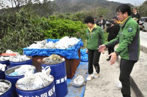 回収された漂着油について説明を受ける渡嘉敷環境副大臣(左)=14日、奄美市名瀬の朝仁海岸