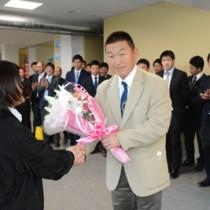 歓迎の花束を受け取る佐々木監督=17日、奄美空港