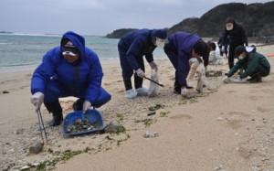 手作業で漂着油の回収を行う県職員ら=11日、和泊町の畦布ワンジョビーチ
