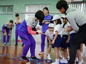 ランニング教室で児童と交流する東北福祉大陸上部の選手たち=21日、田検小