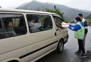 規制区間の入り口で通行証を受け取る認定ガイドの車両=22日、奄美市名瀬知名瀬