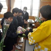 小学生にスプレーギクの花束を贈る研究会のメンバーら=2日、和泊町の内城小