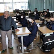 戦争体験を伝える向井さん(左)と講話を聞く生徒ら=8日、天城町天城中学校