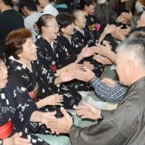 男女が向き合って唄掛けと手踊りを楽しんだ旧正月恒例の「節田マンカイ」=16日、奄美市笠利町節田