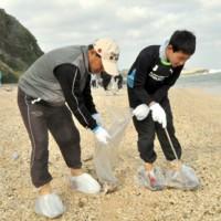 沖泊海浜公園の海岸で、関係機関が合同で行った漂着油などの除去作業=17日、知名町
