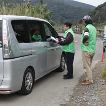 一般車両に乗り入れの自粛を呼び掛ける関係機関の職員ら=16日、奄美市名瀬知名瀬