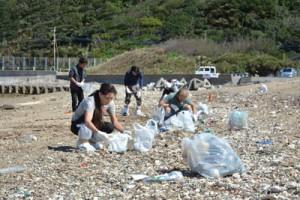 浜辺で油の回収を進める住民ボランティア=18日、奄美市笠利町の海岸