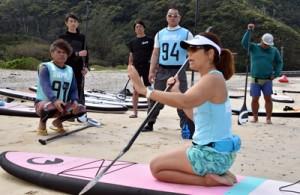 参加者にパドルの持ち方を指導する安さん(右)=14日、奄美市名瀬の朝仁海岸