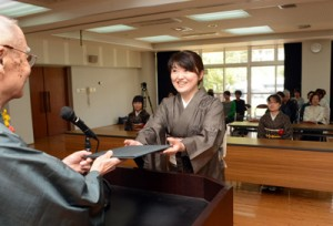 1年間織り技術を学び修了証書を受け取る修了生=28日、奄美市名瀬