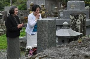 感極まった様子で愛加那の墓前に手を合わせる島津さん(右)と竹内さん=4日、龍郷町龍郷