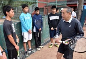 高校生にラケットの構え方をアドバイスする坂井さん(右)=10日、奄美市の名瀬運動公園庭球場