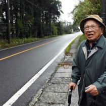 与論島出身者が暮らしていた「よろん坂」に立つ箕作永吉さん=6日、屋久島町