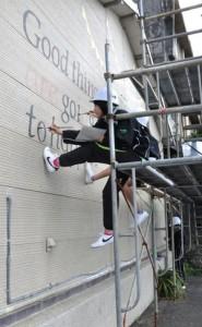 壁にアートを描く徳之島高校美術部の生徒ら=18日、天城町平土野