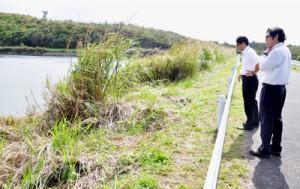ヘリから落下したカーゴドアが発見された草地付近を確認する知名町職員=7日午前10時半ごろ、同町の山田ダム近く