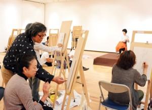 受講生に描き方を説明する西さん(左)=17日、田中一村記念美術館
