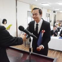 卒業証書を受け取り、浜崎理事長と握手する卒業生=8日、奄美市名瀬