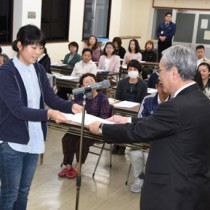 地域通訳案内士の研修修了証を受け取る試験合格者=12日、奄美市名瀬