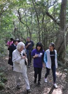 外国人観光客と森を散策する生徒ら=26日、龍郷町の奄美自然観察の森