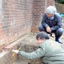 久慈水溜跡のれんがを調査する山岡さん(手前)と鼎さん=6日、瀬戸内町