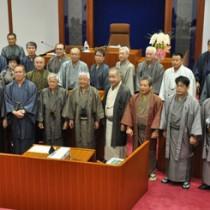 議会閉会後、記念撮影する議員と町幹部=6日、龍郷町議会本会議場