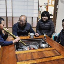 「里親を10年続けるのが目標です」。留学生を受け入れている里親の平園さん夫婦(中央)=1月24日、西之表市