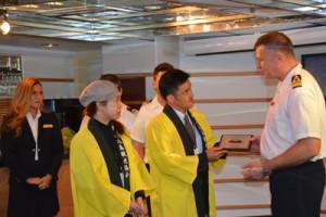 クラシュ船長(右)から記念盾を受け取る越間会長ら=23日、奄美市名瀬