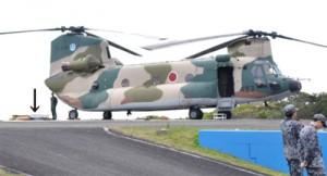 部品落下があったとみられるヘリコプターCH47J。後部側地面(矢印部分)には落下物とみられるカーゴドア=7日午前10時ごろ、知名町の空自沖永良部島分屯基地