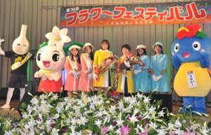新おきのえらぶ島観光大使の委嘱を受けた谷山さんと平山さんを囲んで記念撮影=11日、和泊中体育館