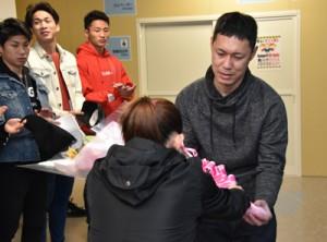 花束を受け取る三浦監督=8日、奄美市笠利町の奄美空港