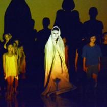 映像、音楽に合わせてパフォーマンスを披露する谷さんと子どもたち=11日、奄美文化センター