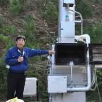 試験運転した小型焼却炉「チリメーサー」と性能を説明する福富社長=13日、龍郷町役場駐車場