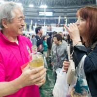 奄美黒糖焼酎を試飲する来場者=15日、京セラドーム大阪