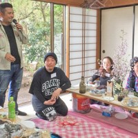 島料理や奄美黒糖焼酎が並んだ会場で花見会を楽しむ東北奄美会の会員ら=15日、福島市