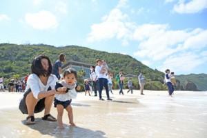 無病息災を祈って海水に子どもの足を浸す家族ら=18日、奄美市名瀬の大浜海浜公園