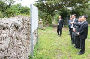「菊次郎生誕の地」に残る石垣を視察する駐福岡台湾総領事館一行ら=16日、龍郷町龍郷