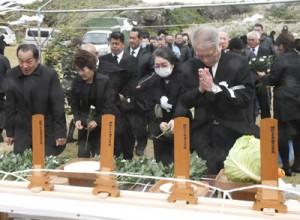 祭壇に献花して犠牲者のみ霊を慰める参列者=7日、伊仙町犬田布岬