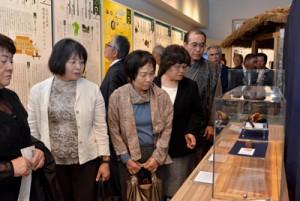 西郷家の歴史や家族の絆を伝える展示品に見入る来場者たち=20日、龍郷町