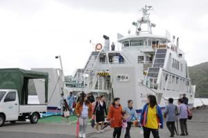 第1便が着岸し、乗船、下船する利用客ら=6日午前7時半ごろ、瀬戸内町加計呂麻島瀬相港