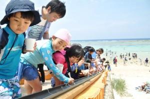 海岸でそうめん流しを楽しむ参加者ら=28日、和泊町のワンジョビーチ