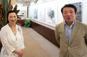 奄美の植物を描き、個展を開いた(左から)曽さん、陳参事官=3月30日 東京銀座の画廊