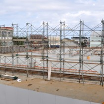 基礎工事が完了し、外部の足場組立て作業などが始まった和泊町の新庁舎建設工事。左の建物が現庁舎=11日、同町