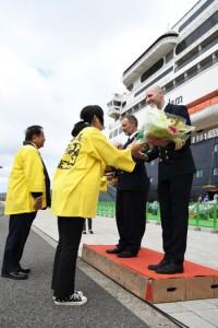 谷会長(後方左)らから花束を受け取るターナー船長ら=13日、奄美市名瀬港観光船バース