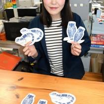 徳之島に生息する動物をデザインしたポストカードと制作者の大間さん=4日、天城町役場