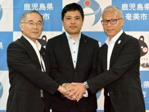 市の職員として㈱NTTドコモから派遣された竹山さん(写真中央)と東副市長(同左)、有田部長=26日、奄美市