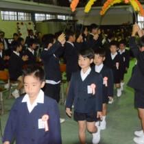 在校生らに見守られ、入場する新1年生=6日、瀬戸内町の古仁屋小体育館