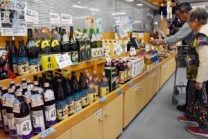 奄美黒糖焼酎を手に取る買い物客=12日、菊池市の特産品センター「七城メロンドーム」