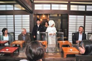 正装で食事会場に「サプライズ」入場する赤崎雄太さん、奈都子さん夫妻=3月19日、奄美市名瀬