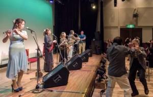 出演者4人の「ワイド節」「六調」で総踊りとなった築地俊造さん追悼コンサート=8日、東京・新宿のホール