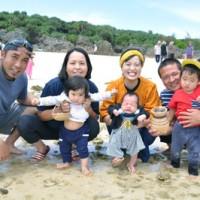いとこ同士でパマクマシュンを体験する勝彩華ちゃん(左側)と高健人ちゃんの家族=18日、与論町赤崎海岸