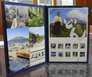 日本郵便が販売開始した「西郷どん」記念切手セット(上)と、大勝郵便局の重原局長(左から2人目)から切手シートを受け取った龍郷町の竹田町長(同3人目)=25日、龍郷町